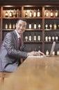 Geschäftsmann working auf laptop wein regal im hintergrund Lizenzfreie Stockbilder