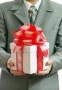 Geschenk in den Händen des Geschäftsmannes Stockfotografie