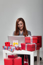 Geschenke in front smiling young woman using laptop Lizenzfreie Stockfotografie