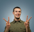 Gesture of peace young happy man with a on a gray background Stock Photography