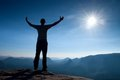 Gesture of triumph. Happy hiker in sportswear. Tall man on the peak of sandstone rock in national park Saxony Switzerland watch do Royalty Free Stock Photo