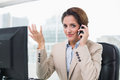 Gesturing businesswoman phoning in bright office Stock Photography