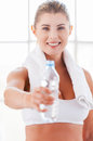 Get refreshed beautiful mature woman in sports clothing stretching out a bottle with water and smiling Royalty Free Stock Photography