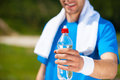 Get refreshed close up of young man stretching out a bottle with water and smiling while standing outdoors Royalty Free Stock Images