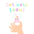 Get well soon. Hand holding a cupcake.