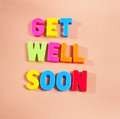 Get well soon text in colorful uppercase letters on beige background Royalty Free Stock Photo
