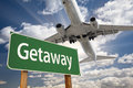 Getaway green road sign and airplane above with dramatic blue sky clouds Royalty Free Stock Photography