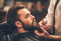 Getting perfect shape close up side view of young bearded man beard haircut by hairdresser at barbershop Stock Images