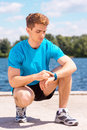 Getting ready to jogging handsome man checking time before on riverbank Stock Photos