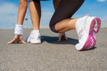 Getting ready to run close up image of woman in sports shoes standing in starting line Stock Photo