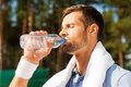 Getting refreshed after game side view of thirsty young man in polo shirt and towel on shoulders drinking water Stock Photos