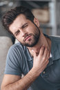 Getting sick frustrated handsome young man touching his neck and keeping eyes closed while sitting on the couch at home Stock Photos