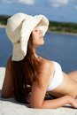 Getting tanned image of female in white bikini and hat sunbathing on sandy beach during vacation Stock Photos