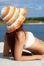 Getting tanned image of female in white bikini and hat sunbathing on sandy beach during vacation Royalty Free Stock Image