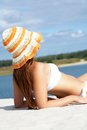 Getting tanned image of female in white bikini and hat sunbathing on sandy beach during vacation Royalty Free Stock Photo