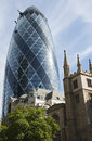 The gherkin building london shines against a blue sky behind st andrew undershaft s church designed by norman foster city s first Royalty Free Stock Photography