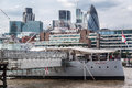 The gherkin london modern architecture building in downtown and hms belfast ship on thames river in first plane Royalty Free Stock Image