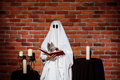 Ghost holding book over brick background. Halloween party. Royalty Free Stock Photo
