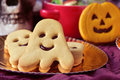 Ghost shaped and pumpkin shaped cookies for halloween closeup of a golden tray with some a cookie a bowl with candies a scary Royalty Free Stock Photography