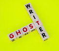 Ghost writer text and inscribed in uppercase letters on small white cubes and arranged in crossword style with common letter t Stock Image