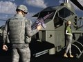 Gi flirting with female helicopter mechanic modern soldier in combat uniform and carrying automatic weapon who leans against the Royalty Free Stock Photos