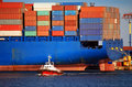 Giant Blue Container Ship and Small Red Tugboat Royalty Free Stock Photo