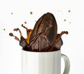 Giant coffee bean splashing in mug close up view at white background Royalty Free Stock Photo