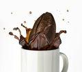 Giant coffee bean splashing in mug close up view at white background Royalty Free Stock Photo
