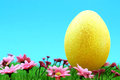 Golden easter egg on a meadow with pink flowers Royalty Free Stock Photo