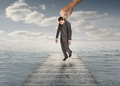 Giant hand holding a businessman by his jacket over the sea Royalty Free Stock Images