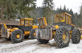 Giant logging vehicles in the winter forest