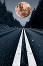 Giant red full moon and lonely road large surreal hovering above a country trees forest Stock Photos