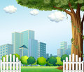 A giant tree near the wooden fence across the tall buildings illustration of Royalty Free Stock Photos