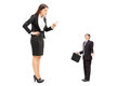 Giant woman threatening a tiny businessman women isolated on white background Royalty Free Stock Images