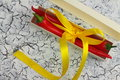 Gift with bitterness on a wooden board in a box are the peppers decorated ribbon Stock Image