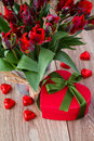 Gift boc with bouquet of red tulips heart box on wooden table Stock Photos