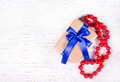 Gift box with blue bow and red coral beads on a white wooden background. Royalty Free Stock Photo