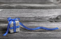 Gift box with blue checked ribbon on wooden grey background. Royalty Free Stock Photo