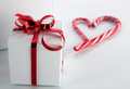 Gift box with candycane white red bright bow and heart on light background Stock Images