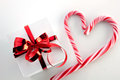 Gift box and candycane white with red bright bow heart on light background top view Royalty Free Stock Photo