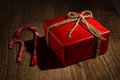 Gift box and candycane on wooden background Stock Images