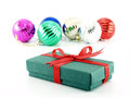 green gift box with red bow ribbon and pile of colorful glossy christmas balls isolated on white background
