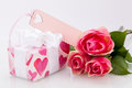 Gift box with an empty tag next to three roses close up of a wrapped in decorative paper pattern heart shapes symbol of Stock Image