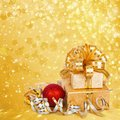 Gift box in gold wrapping paper on a beautiful abstract background Royalty Free Stock Photography