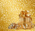 Gift box in gold wrapping paper on a beautiful abstract background Royalty Free Stock Images