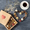 Gift box of gourmet chocolates for Valentine`s Day on dark background with cup of coffee, top view, copy space