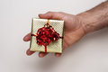 Gift box man s hand holding a small with a ribbon around the Royalty Free Stock Image