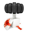 Gift box with red band and car tires on spring on isolated white background Stock Image