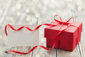 Gift box with red bow ribbon and empty paper note on table for Valentines day Royalty Free Stock Photo