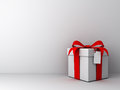 Gift box with red ribbon bow and blank tag on empty white wall background abstract Stock Image